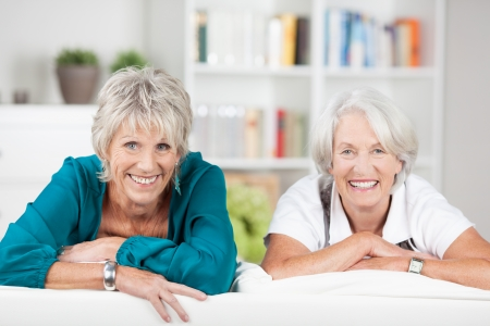 Two beautiful senior ladies with beaming friendly smiles looking at the camera over the back of a sofa in the living room photo