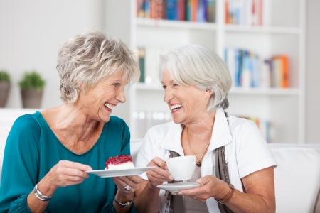 Twee aantrekkelijke oudere dames genieten van een kopje thee zitten kletsen en lachen samen in een woonkamer Stockfoto