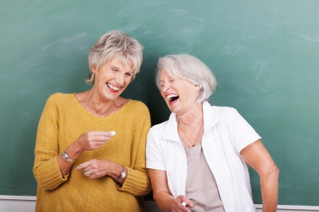 jokes: Two senior women sharing a good joke standing together in front of a green blackboard laughing uproariously