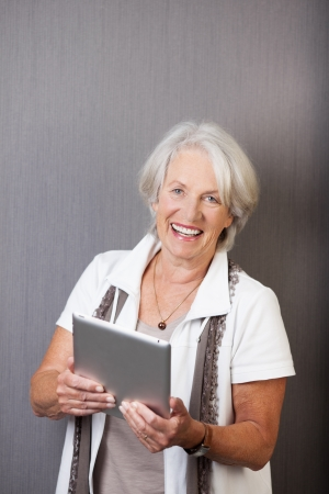 browses: Vivacious elderly woman with a tablet computer in her hands laughing as she connects to social media or browses the internet Stock Photo