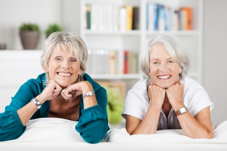 retirement community: Two attractive grey-haired elderly women relaxing at home in the living room leaning over the back of the sofa smiling at the camera