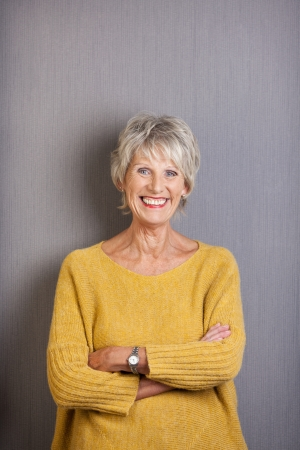Beautiful elderly lady with a vivacious smile standing with her arms folded grinning happily at the camera in a loose trendy pullover photo