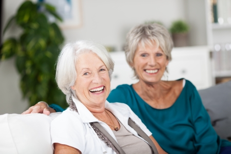 Laughing vivacious senior women relaxing at home sitting together on a sofa relaxing and enjoying each others company