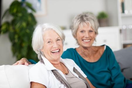 companionship: Riendo mujeres mayores vivaces relaja en el país sentados juntos en un sofá de relax y disfrutar de la compañía del otro Foto de archivo