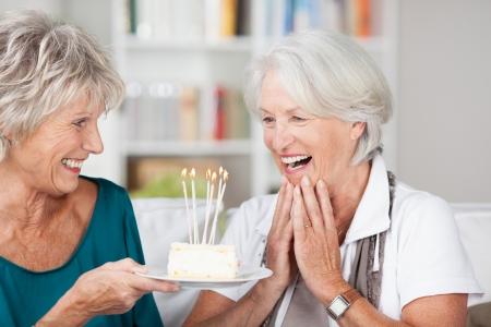 riÃ â  on: Mujer mayor que celebra su cumpleaños se entregó un pastel con velas encendidas por su amiga y aplaudiendo con sorpresa y agradecimiento Foto de archivo