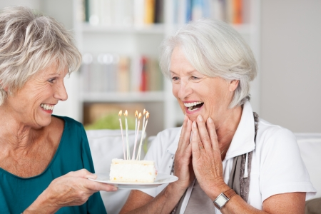 mature old generation: Senior woman celebrating her birthday being handed a cake with burning candles by her friend and clapping her hands in surprise and appreciation