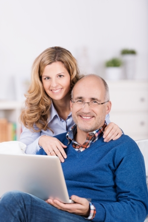 Smiling affectionate couple using a laptop with the wife standing behind her seated husband with her arms around his shoulders as they smile at the camera photo