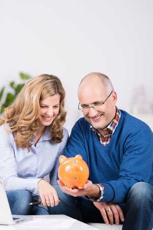 family budget: Couple gazing at their piggy bank with a smile of anticipation as they sit in the living room planning to fulfill one of their dreams