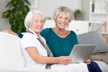 Two elderly ladies sharing a laptop computer as they relax together on a comfortable sofa in a living room photo