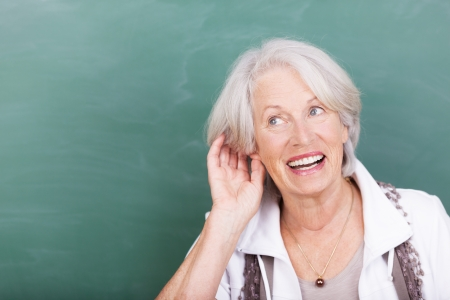 Elderly lady with hearing problems holding her hand to her ear as she struggles to hear against a green background with copyspace