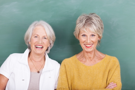 Two vivacious attractive elderly ladies standing side by side laughing at the camera against a green blackboard Stock Photo - 24459114