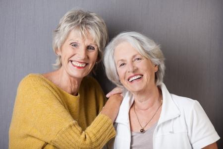 mujer alegre: Dos se�oras mayores felices vivaces riendo juntos mientras comparten un momento especial en su amistad de toda la vida