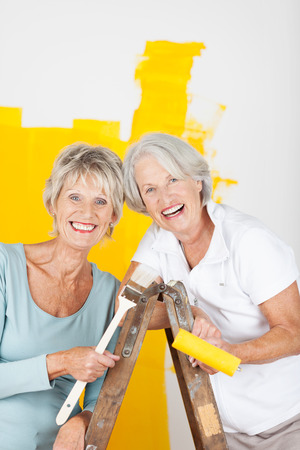 Two happy elderly women painting the house laughing with pleasure as they stand on a wooden stepladder with a half painted yellow wall behind them