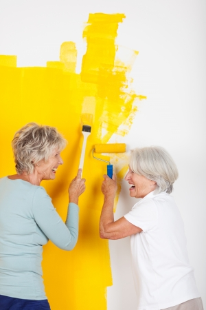 Two senior women having fun painting a wall with modern bright yellow paint standing laughing at their handiwork photo