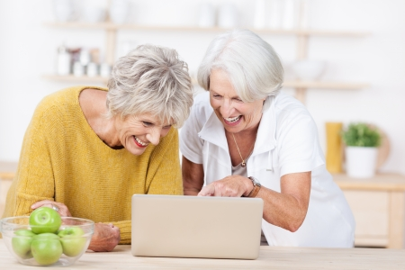 Two vivacious attractive senior women surfing the internet on a laptop computer laughing as they point to the screen photo
