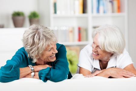 retirement community: Two elderly female friends having a chat laughing as they relax together on a sofa in the living room