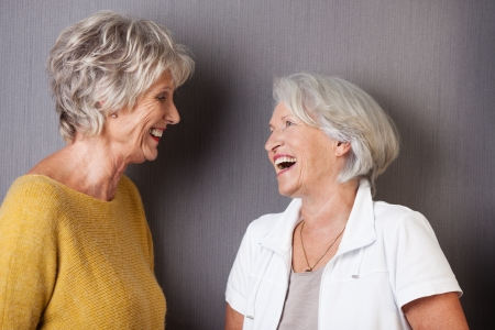 Two elderly female friends sharing a joke standing laughing and facing each other in front of a grey background Stock Photo