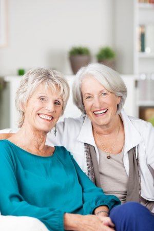 mature women: Two happy laughing senior women friends sitting on a sofa in the living room smiling at the camera with optimism