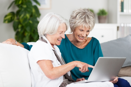 Two senior women surfing the internet laughing and exclaiming as they point to something on the screen while sitting side by side on a sofa in the house photo