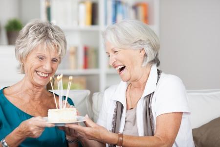 giggle: Riendo atractivas se�oras mayores celebran un cumplea�os que sostiene una placa con un peque�o pastel con velas encendidas como ellos se r�en con el disfrute Foto de archivo