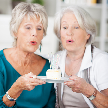 gasp: Two elderly women eyeing a piece of delicious cake on a plate that they are both holding with big round eyes making a gasp of anticipation