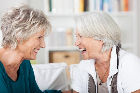 amigas conversando: Dos feliz atractiva mujer mayor de pelo gris disfrutar de una risa juntos mientras se sientan en un sofá en la sala de estar