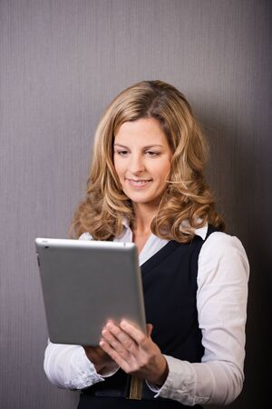 browses: Beautiful young blond businesswoman smiling as she browses the internet on her tablet computer while standing against a grey background