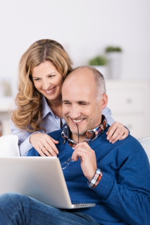 Couple smiling as they surf the internet or interact with their friends on social media on a laptop computer while relaxing in the living room photo