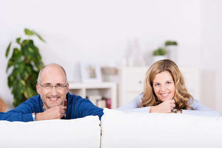 Relaxed confident smiling man and woman relaxing at home in the living room smiling over the top of the sofa at the camera photo