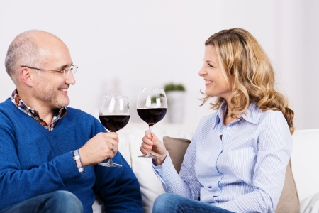 Attractive couple celebrating over a glass of wine sitting in the living room looking at each other with happy smiles as they raise their glasses in a toast photo