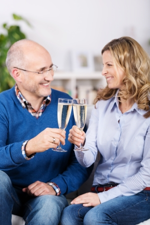 Happy couple celebrating with champagne sitting smiling into each others eyes while clinking their glasses in a toast photo