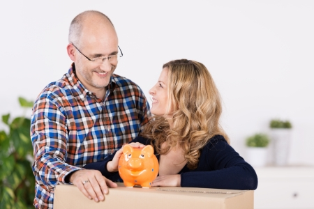 Man and woman with a carton and piggy bank smiling as they plan the redecorating of their new home after moving house photo