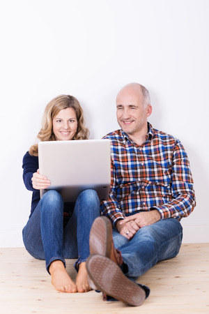 Husband and wide relaxing with a laptop computer sitting on a wooden floor with their backs against a white wall reading something together on the screen photo