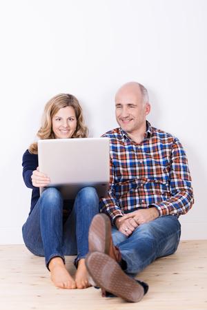 echtgenoot: Man en brede ontspannen met een laptop computer zittend op een houten vloer met hun rug tegen een witte muur samen iets lezen op het scherm