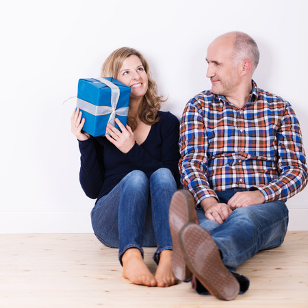 Beautiful smiling young woman trying to guess what is in her gift as she sits barefoot on a wooden floor alongside an attractive older man photo
