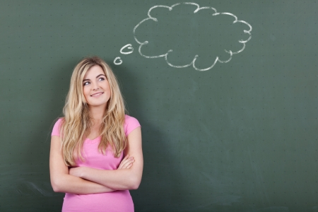 Young schoolgirl with an idea standing confidently in front of the chalkboard