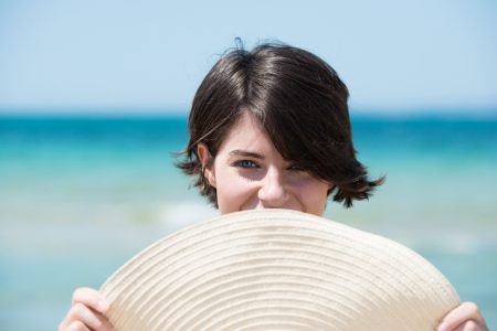 obscuring: Beautiful young woman at the seaside standing with the brim of her straw sunhat obscuring her mouth smiling  Stock Photo