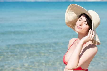 Young woman, in bikini and floppy sun hat, stands on the beach by clear turquoise sea, and enjoys the summer warmth. 版權商用圖片