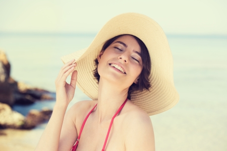 eye's closed: Cute young woman in a straw sunhat posing with a beautiful smile and her eyes closed in enjoyment on a beach Stock Photo