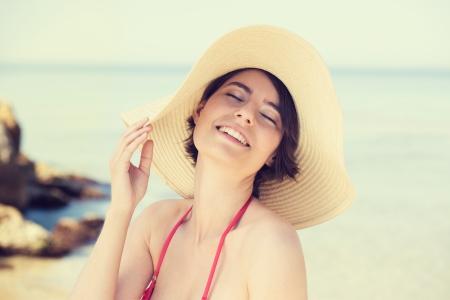 ojos cerrados: Mujer joven linda en un sombrero de paja posando con una hermosa sonrisa y los ojos cerrados en el disfrute en una playa
