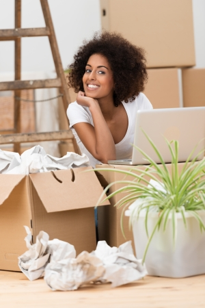 Attractive African American woman unpacking boxes in her new home sitting on the floor in the living room smiling at the camera photo