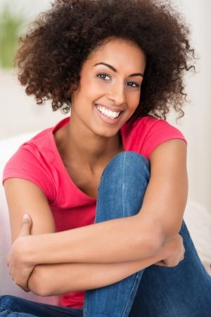 emotions faces: Smiling African American Frau mit Afro-Frisur sitzt umarmt ihre Knie und strahlt in die Kamera