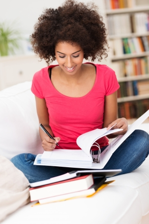 lotus position: African American woman sitting on the sofa in the lotus position while studying hard and taking notes from the books