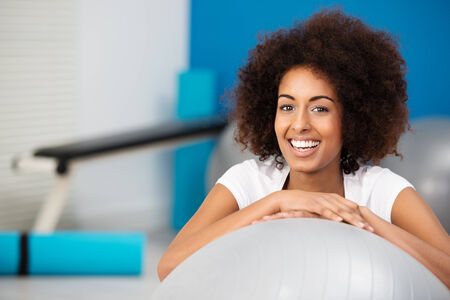 mixed race woman: Smiling beautiful African American woman with a curly afro hairstyle in a gym leaning on a pilates ball