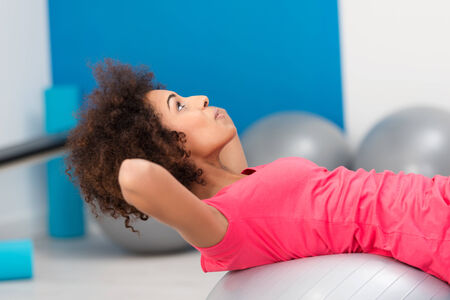 Young African American woman doing Pilates arching her back over the gym ball to strengthen her muscles photo