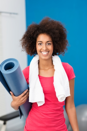 skinny woman: Athletic African American woman arriving at the gym with her aerobics mat under her arm pausing to give the camera a lovely friendly smile Stock Photo