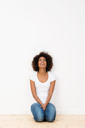 woman kneeling: Attractive African American woman kneeling on the hardwood floor of her new house looking up into the air and laughing with pleasure Stock Photo