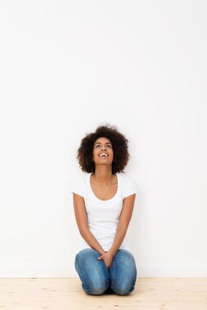 donna in ginocchio: Attraente donna afro-americana in ginocchio sul pavimento di legno duro della sua nuova casa guardando in aria e ridendo con piacere Archivio Fotografico