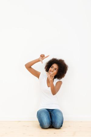 donna in ginocchio: Bella giovane donna afro-americana in ginocchio sul pavimento di legno duro del suo nuovo appartamento a visualizzare il suo nuovo arredamento facendo una cornice con le dita Archivio Fotografico