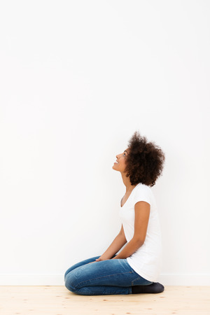 woman kneeling: African American woman kneeling on the floor looking at a white wall in her new house as she visualises her new colour scheme and decor, with copyspace Stock Photo